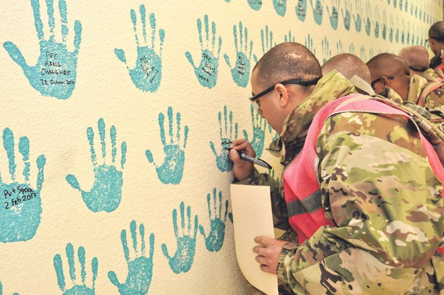 Soldiers in the 701st Military Police Battalion sign a SHARP wall in their battalion headquarters building as a symbol of the pledge they took during SHARP training.