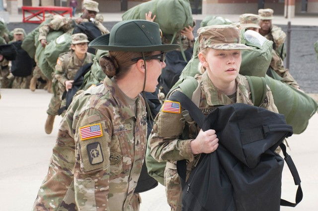 Staff Sgt. Cassidy White, Co. C, 31st Engr. Bn. drill sergeant, left, motivates a new Co. D Soldier to move faster during 'training day zero'.