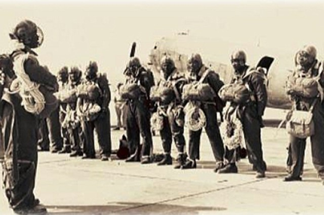 """Paratroopers of the U.S. Army's 555th Parachute Infantry Battalion stand at ease during inspection. The men were issued """"let-down"""" ropes and football helmets with face masks to assist during forest landings while detailed to the U.S. Forest Service, where they served as """"smokejumpers"""" at the end of World War II."""
