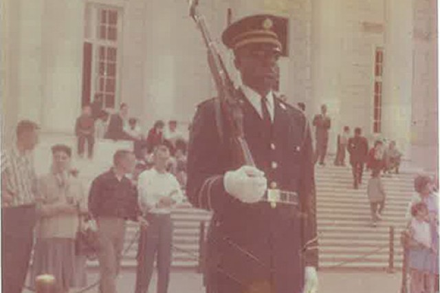 """Then-Spc. 4th Class Fred Moore faces the Tomb of the Unknown Soldier during his relief walk, 1961. Moore was the first African-American Soldier to """"walk the mat"""" at the Tomb."""