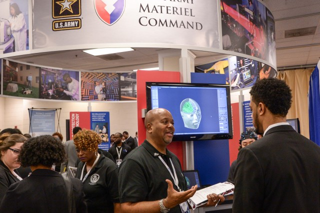 Clifford Holmes, from the U.S. Army Armaments Research, Development and Engineering Center, greets a young STEM student at the Army Materiel Command exhibit at the 31st annual Black Engineer of the Year Awards Conference in Washington, D.C.