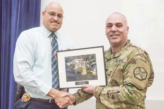Chief James Hicks, the Town of Natick's police chief, receives a token of appreciation from Lt. Col. Ryan Raymond, United States Army Garrison Natick commander, after speaking to the Natick Soldier Systems Center workforce, Feb. 8.