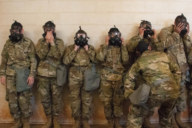 Soldiers in Company E, 1st Battalion, 48th Infantry Regiment test the seal on their protective masks in the gas chamber.