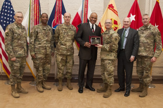 Maj. Gen. Edward Daly, commanding general, U.S. Army Sustainment Command, presents Chief Warrant Officer 4 Phillip Brashear, U.S. Army Reserve helicopter pilot and son of famous Navy master diver Master Chief Petty Officer Carl Brashear, with an appreciation plaque for serving as keynote speaker at the National African American History Month Observance in Heritage Hall at Rock Island Arsenal, Illinois, Feb. 14.