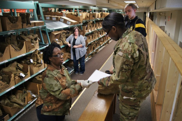 Flora Shelton, lower left, a Logistics and Readiness Center boot and shoe fitter at Fort Leonard Wood's 43rd Adjutant General Battalion, instructs Pvt. Qalexus Taylor, upper left, as she receives her initial uniform issue Feb. 2, 2017; while Renee Cox, lower right, LRC Clothing Issue supervisor, and Pfc. Kesyanda Trader, upper right, observe.