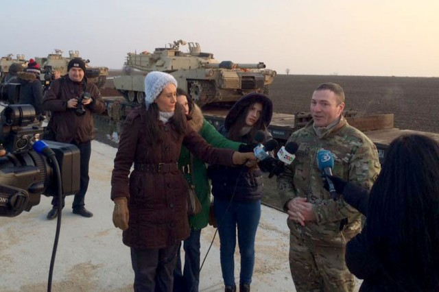 MAJ Scott Stephens, executive officer, 1st Battalion, 8th Infantry Regiment, 3rd Armored Brigade Combat Team, 4th Infantry Division, fields questions from Romanian journalists who were present for the arrival of the first 15 tanks to Mihail Kogalniceanu Air Base, Romania, Feb. 14, 2014. The arrival of the tanks and roughly 500 soldiers from 1st Bn., 8th Inf. Regt., marks the beginning of a continuous presence of ABCT's in southeastern Europe as part of Atlantic Resolve.