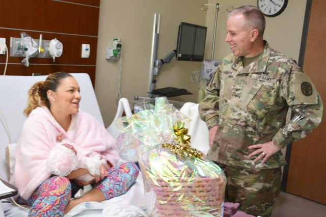 Col. Mark Thompson, commander, Carl R. Darnall Army Medical Center, congratulates Thalia Figueroa on the arrival of her daughter, Lyah Giuliet, who has the double distinction of being the hospital first 2017 baby and CRDAMC's first New Year's baby since the hospital opened April 3, 2016.