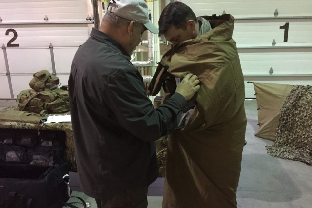 Sgt. 1st Class Travis Baie, the operations noncommissioned officer  for U.S. Army Alaska's Northern Warfare Training Center, is given a demonstration of a ThermaShield blanket by retired Army sergeant major Frank Arellanes with ForceProtector Gear at the Extreme Cold Weather/High Altitude Symposium on Fort Wainwright, Alaska, Feb. 13, 2017. The symposium brings together U.S. military, academia and industry experts to discuss equipment, concerns and solutions for operating effectively in ECW/HA environments. (Photo by Capt. Richard Packer, U.S. Army Alaska Public Affairs)