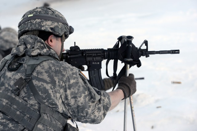 A Soldier uses ski poles to create a bipod firing position.