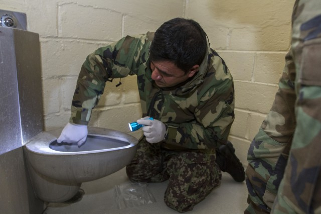 An Afghan National Army student searches a cell during a practical exercise needed for graduation.