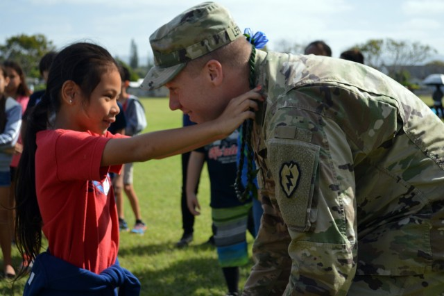 Staff Sgt. Wesley Lefavour, a section leader assigned to 3rd Squadron, 4th Cavalry Regiment, 3rd Brigade Combat Team, 25th Infantry Division, receives a ti leaf lei from a student at Ka'ala Elementary School, Wahiawa, Hawaii, on Feb. 1, 2017. Lefavour described Army life, and let students to wear the Improved Outer Tactical Vest (IOTV) and Advanced Combat Helmet (ACH) during the school's career day. (U.S. Army photo by Staff Sgt. Armando R. Limon, 3rd Brigade Combat Team, 25th Infantry Division)