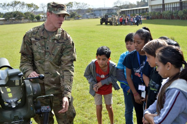 Spc. Charles Moss, a cavalry scout assigned to 3rd Squadron, 4th Cavalry Regiment, 3rd Brigade Combat Team, 25th Infantry Division, shows schoolchildren how the Improved Target Acquisition System (ITAS) works at Ka'ala Elementary School, Wahiawa, Hawaii, on Feb. 1, 2017. Moss was one of a dozen Soldiers at the school's career day discussing what the Army is like to the students. (U.S. Army photo by Staff Sgt. Armando R. Limon, 3rd Brigade Combat Team, 25th Infantry Division)