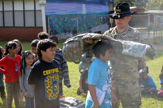 First Lt. Colin Hauer, signal officer assigned to 3rd Squadron, 4th Cavalry Regiment, 3rd Brigade Combat Team, 25th Infantry Division, helps put on an Improved Outer Tactical Vest (IOTV) on a school child at Ka'ala Elementary School, Wahiawa, Hawaii, on Feb. 1, 2017. Hauer was one of a dozen Soldiers at the school's career day discussing and showing what the Army is like to the students. (U.S. Army photo by Staff Sgt. Armando R. Limon, 3rd Brigade Combat Team, 25th Infantry Division)