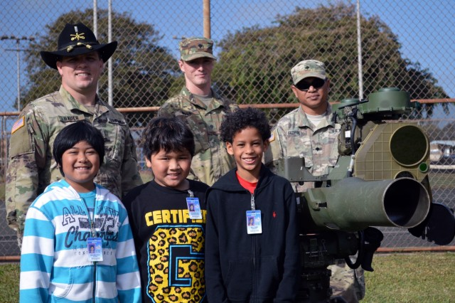 Soldiers assigned to 3rd Squadron, 4th Cavalry Regiment, 3rd Brigade Combat Team, 25th Infantry Division, and students from Ka'ala Elementary School stand together next to an Improved Target Acquisition System (ITAS) during the school's career day event at Wahiawa, Hawaii, on Feb. 1, 2017. The Soldiers interacted with the students by talking about Army life, what they do and the kind of equipment they use while out in the field. (U.S. Army photo by Staff Sgt. Armando R. Limon, 3rd Brigade Combat Team, 25th Infantry Division)
