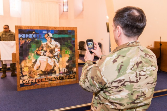 """LANDSTUHL, Germany - Col. William Stubbs, commander, 30th Medical Brigade, takes a photo of a painting made by children of the 212th Combat Support Hospital entitled """"Care for the Wounded"""", February 15, 2017.  (U.S. Army photo by Maj. Chris N. Angeles, 212th Combat Support Hospital Public Affairs)"""