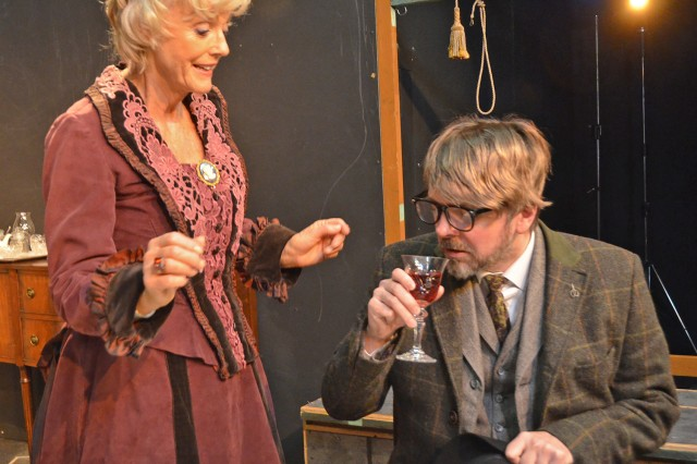 "Bobbie Lording-Pfanner serves up a deadly glass of wine to Erik Kraemer during rehearsals for the Amelia Earhart Playhouse's ""Arsenic and Old Lace."""