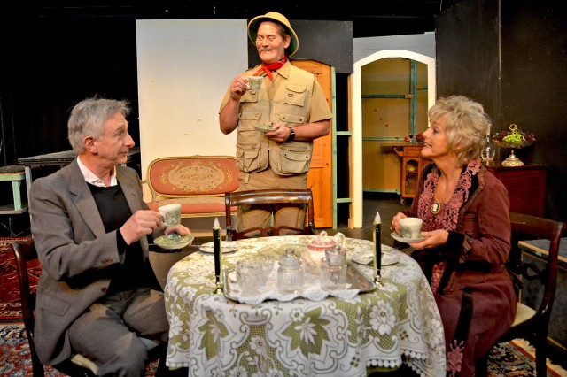"The Brewsters enjoy a spot of tea with a visitor in ""Arsenic and Old Lace."""