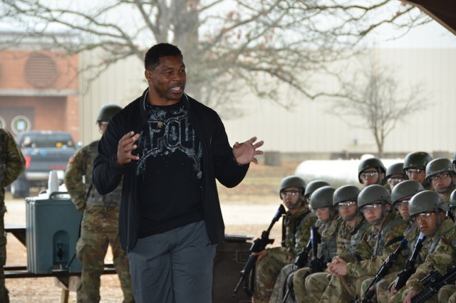 Herschel Walker, left, provides a motivational speech to Company A, 701st Military Police Battalion Soldiers during a break from marksmanship training Tuesday.