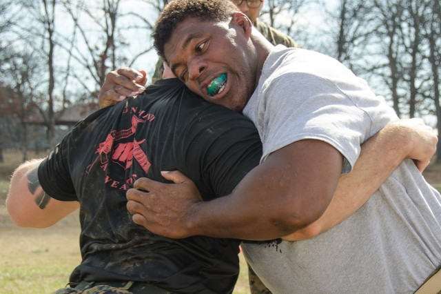 Herschel Walker, right, grapples with a Marine from the Fort Leonard Wood Marine Corps Detachment during martial arts exposure and physical fitness experience Wednesday during his visit.