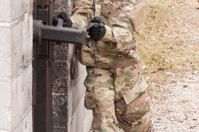 A Sapper Leader Course 06-17 student attempts to ram a door during urban breaching operations Monday.