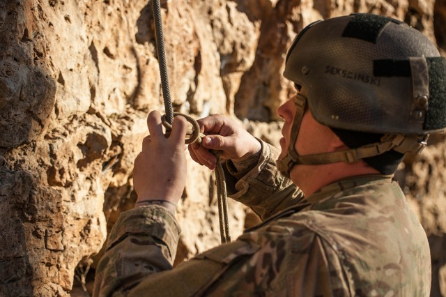 A Sapper Leader Course 06-17 student ties a prusik knot before climbing a short wall during mountaineering operations Feb. 17.