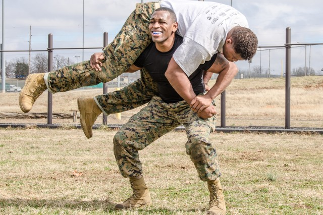 Marine Gunnery Sgt. Maurice Morrison, Fort Leonard Wood Marine Corps Detachment assistant operations chief, lifts 220-pound Herschel Walker, during martial arts exposure and physical fitness experience Wednesday.