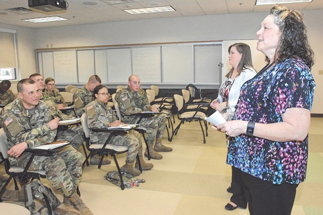 From right, Tammy Fink, ACS financial readiness specialist, assisted by Sandra Lenzmeier, Armed Forces Bank manager, provides a Military Saves briefing to Company C, 701st Military Police Battalion Soldiers Feb. 10.