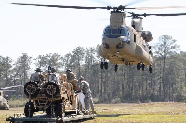 Soldiers of the 7th Special Forces Group out of Eglin Air Force Base, Florida, prepare to attach a loaded flat rack to a CH-47 Chinook as they conduct sling-load training with B Co., 1-223rd Avn. Regt. Feb. 16.