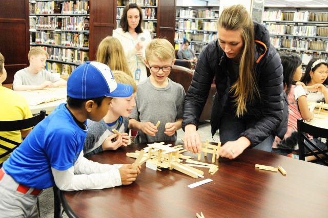 Family members work together on their construction projects during the Mad Scientist Workshop at the Fort Rucker Center Library Feb. 16.