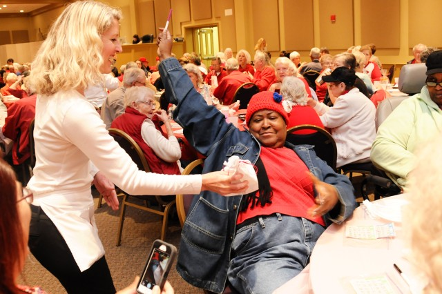 Madea Page, of the Daleville Senior Center, accepts her door prize during the Fort Rucker Community Spouses Club Sweetheart Bingo event at Hillcrest Baptist Church in Enterprise Feb. 14.