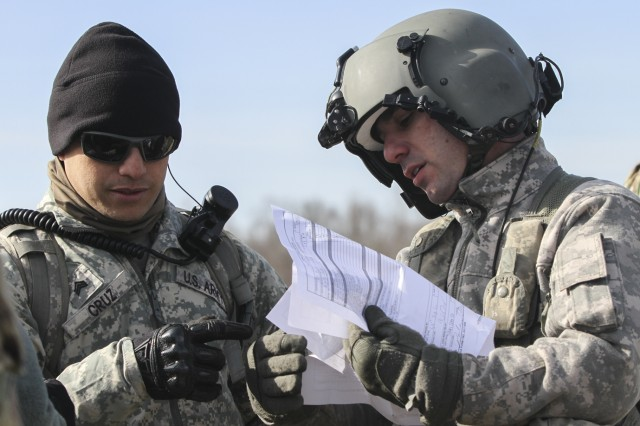 Sgt. Timothy Cruz, left, noncommissioned officer in charge of a sling load training operation for 58th Signal Company, 101st Special Troops Battalion, 101st Airborne Division (Air Assault) Sustainment Brigade, 101st Abn. Div., goes over paperwork with a CH-47 Chinook helicopter pilot from 101st Combat Aviation Brigade, 101st Abn. Div., before the company's sling load operation Feb. 10, 2017, on Fort Campbell, Kentucky. Cruz validated 22 air assault qualified Soldiers in their ability to rig and transport equipment via sling load. (U.S. Army photo by Sgt. Neysa Canfield/101st Airborne Division Sustainment Brigade Public Affairs)