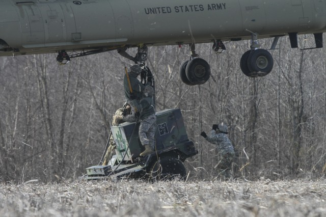 Soldiers from 58th Signal Company, 101st Special Troops Battalion, 101st Airborne Division (Air Assault) Sustainment Brigade, 101st Abn. Div., attach a 10k generator to a CH-47 Chinook helicopter during the company's sling load operation Feb. 10, 2017, on Fort Campbell, Kentucky. Soldiers teamed up in groups of three during the training to validate their ability to rig and transport signal equipment. (U.S. Army photo by Sgt. Neysa Canfield/101st Airborne Division Sustainment Brigade Public Affairs)