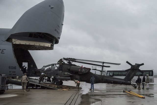 An AH-64 Apache helicopter is unloaded from a C-5M Galaxy airplane at Ramstein Air Base, Germany, Feb. 22 in support of Operation Atlantic Resolve. Four Apache helicopters were transported in the belly of two U.S. Air Force C-5M Galaxy aircraft during this mission.