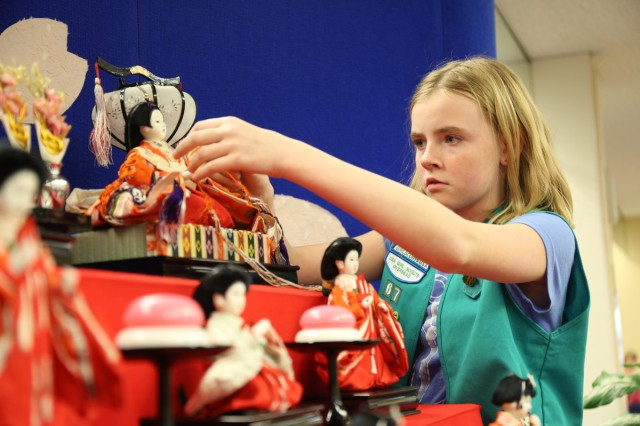 Lena Cook, 11 years old, member of Camp Zama Girl Scouts places accessories into a Hina Doll's hand while setting up Hina Dolls Feb. 23 in the CZ library to help celebrate Hina Matsuri - the Doll Festival March 3 in Japan. (U.S. Army Photos by Noriko Kudo)