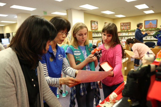 Members of Camp Zama Girl Scouts and Camp Zama librarians check a picture to set up Hina Dolls correctly Feb. 23 in the CZ library to help celebrate Hina Matsuri - the Doll Festival March 3 in Japan. (U.S. Army Photos by Noriko Kudo)