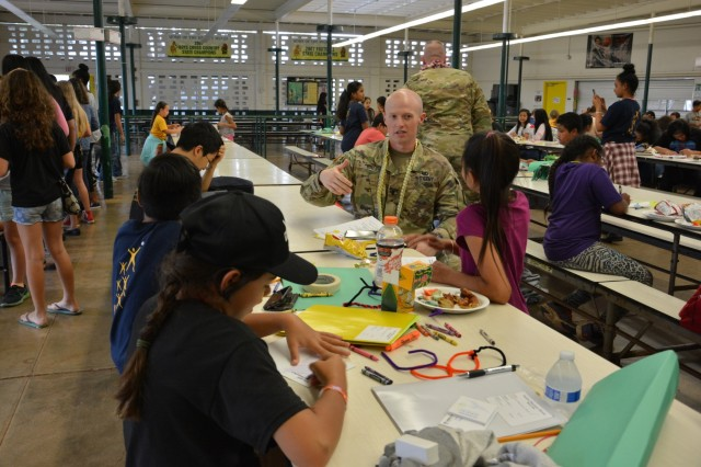 WAHIAWA, Hawaii- Rear Detachment Commander, 1st Lt. Jacob Bales, 552nd MP Company, 728th Military Police Battalion, 8th MP Brigade, 8th Theater Sustainment Command, sits down with a group of Advancement Via Individual Determination (AVID) students Feb. 18, at Leilehua High School, here to answer any questions while the students write personal notes to place inside the care packages they plan on sending to the deployed Soldiers of 552nd MP Co. who are currently deployed in Guam.