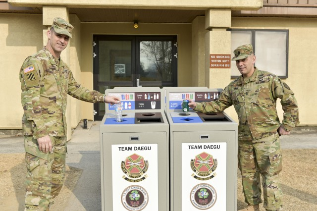 United States Army Garrison Daegu Commander Col. Ted Stephens and Command Sgt. Maj. Juan A. Abreu test the new recycling bins that will be installed into the barracks on Camp Henry January 20.