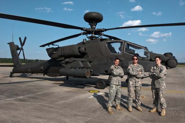 1st Lt. Jenna Pitcher and Staff Sgt. Lauren Rhodes assist U.S. Army Chief Warrant Officer Deborah Glenn, Company B, 1-151st Attack and Reconnaissance Battalion, South Carolina Army National Guard, on a AH-64D Apache helicopter at McEntire Joint National Guard Base in Eastover, South Carolina, August 4, 2015.