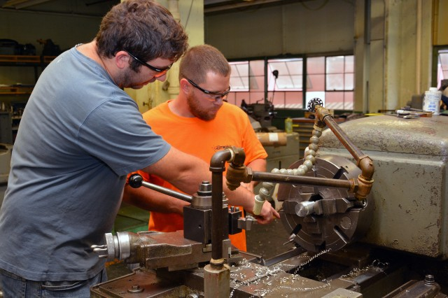 As early as the week that apprentices make their first machining cut, they are coached by senior machinists, such as seen here with machinist Jonathan Morehouse, left, assisting apprentice Todd Herold in Sept. 2016.