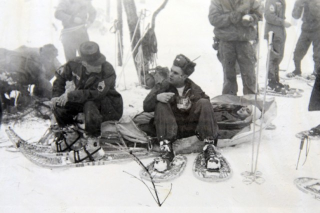 "Army Sgt. 1st Class Henry ""Hank"" Dube (left) on an ahkio (sled) in the 1960s as an instructor at Northern Warfare Training Center, Alaska, chats with a student."