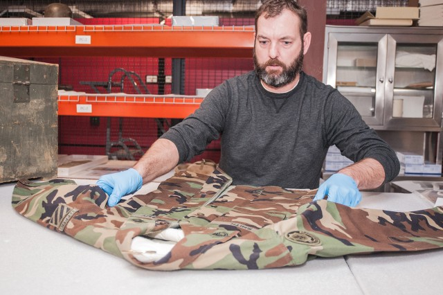 Scott Franklin, U.S. Army Engineer Museum curator, prepares a uniform recently donated to the museum for storage.