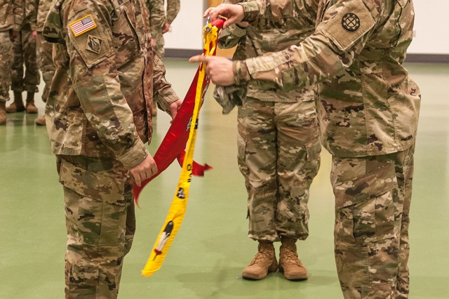 Capt. Curtis Million, 509th Clearance Company commander, left, and Company 1st Sgt. Jamie Swift unfurl the company guidon during the company redeployment ceremony Friday at Nutter Field House.