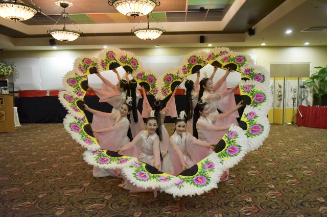 Traditional fan dance per formers make a heart shape with their fans during their performance at the Lunar New Year Reception.
