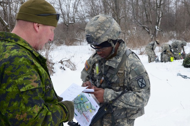 Warrant Officer Matt Edwards, a member of Squadron D, Royal Canadian Dragoons, instructs Pfc. LaMichael Coats, a scout with A Troop, 3rd Squadron, 71st Cavalry Regiment, on what Coats and his team must accomplish during the Canadian lane of the spur ride.