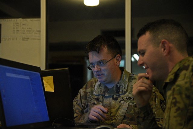 Staff Sgt. Anthony Striang, interactive operator, and Sgt. 1st Class Carl Whitaker, host analyst, 154th Cyber Protection Team, Fort Gordon, Ga., prepare for the early-morning start of a live cyber exercise at Muscatatuck Urban Training Center in Butlerville, Ind., on January 10.