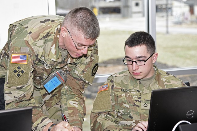Maj. Joseph Marty 154th Cyber Protection Team detachment chief shows the newest member, Pfc. James Olds, how to deal with a problem during a live cyber exercise at Muscatatuck Urban Training Center in Butlerville, Ind., on January 10.