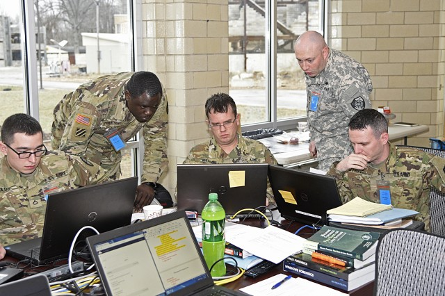 Pfc. James Olds, Chief Warrant Officer 3 Charles Frierson, Sgt. 1st Class Carl Whitaker, Chief Warrant Officer 2 Joshua Neely, and Staff Sgt. Anthony Striang, all of the 154th Cyber Protection Team, Fort Gordon, Ga., work together on a problem during a live cyber exercise at Muscatatuck Urban Training Center in Butlerville, Ind., on January 10.