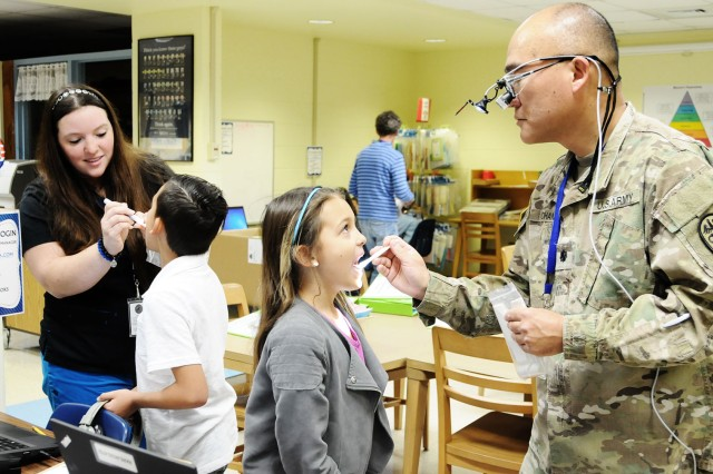 Lt. Col. Chun Chan, Brown Dental Clinic commander, and Jessica Moore, registered dental assistant, perform screenings on Poppy and Gunnar Clagg, third grade students at Fort Rucker Elementary School, Feb. 24.
