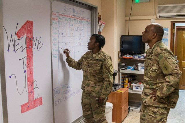 U.S. Army Lt. Col. Trina Rice, human resources officer in charge, Combined Joint Forces Land Component Command -- Operation Inherent Resolve, from New York City, and U.S. Army Chief Warrant Officer 3 Nicholas Rimmer, strength officer, CJFLCC-OIR, from Grenada, Mississippi, write down mileages on the '2,017 Miles in 2017' chart. The team tracks their mileage using the large chart in their waiting room so everyone can see everyone's progress. The team is taking on this challenge to stay physically fit and increase espirit de corps.