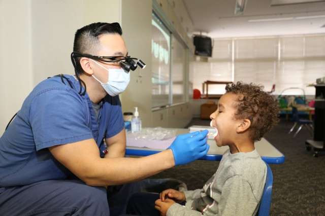 Capt. James Lee, general dentist assigned to DENTAC-Japan, conducts an oral health screening with Corey Miller, 5, kindergartener at Arnn, March 2 for NCDHM. (U.S. Army photo by Lance D. Davis)